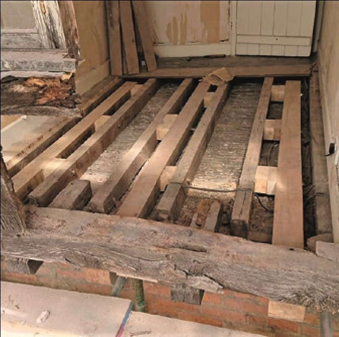 A dismantled timber frame with new jetty joists bolted in