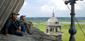 Two carpenters admire the view from a pitched wooden roof, Church of the Transfiguration, Turchasovo